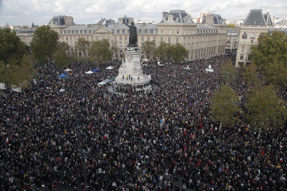 Manifestantes se reúnem na Praça da República, em Paris, neste domingo (18) para marchar em homenagem ao professor de história decapitado em um ataque extremista — Foto: Michel Euler/AP