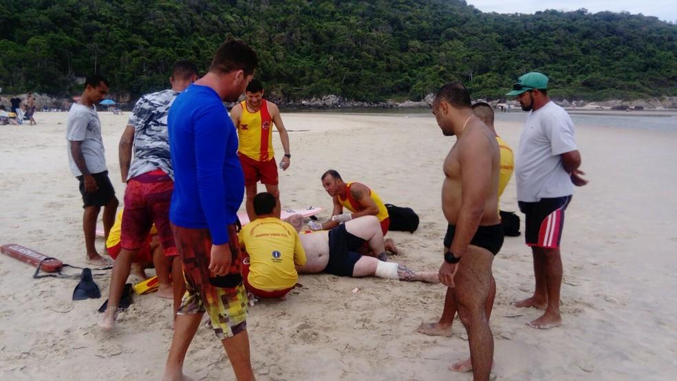 Vítima já sendo resgatada na areia: de sunga preta, o policial Victor Bonfim, herói do dia (Foto: Divulgação/Corpo de Bombeiros)