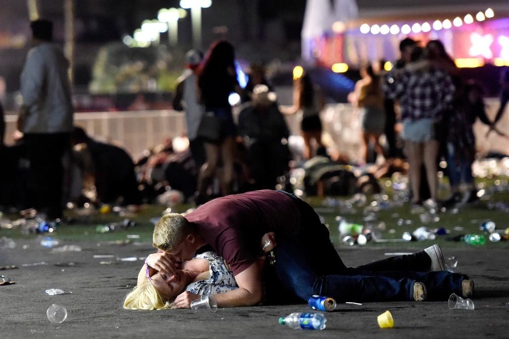 Um casal é visto após tiros serem disparados sobre uma multidão que assistia um show de música country em Las Vegas, nos EUA (Foto: David Becker/Getty Images/AFP)