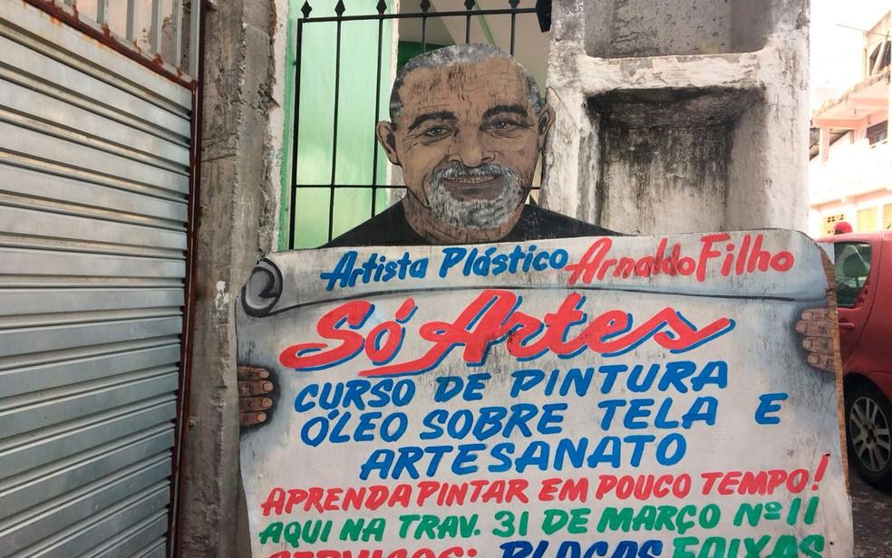 Auto-retrato feito por Nadinho, para divulgar o próprio trabalho, na entrada da rua onde morava em Candeias (Foto: Juliana Almirante/G1)