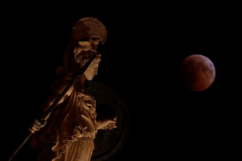 Lua de sangue durante eclipse; na imagem, estátua de Athena na Grécia. (Foto: Costas Baltas/Reuters)