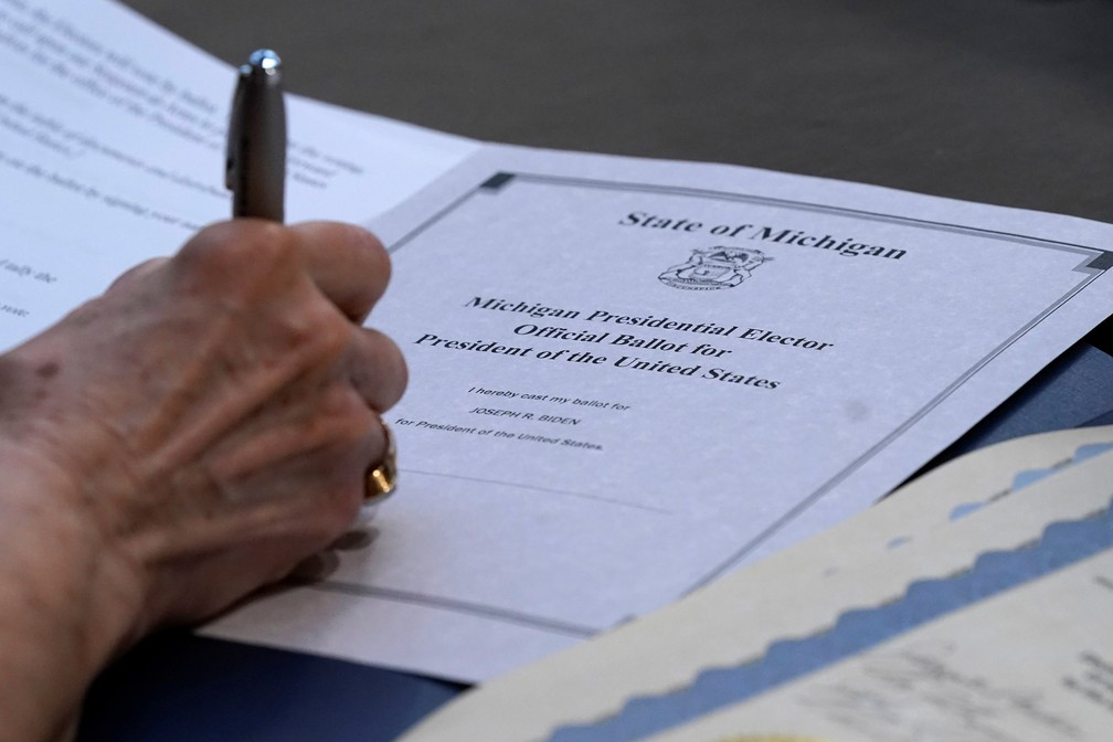 Delegada Bobbie Walton, de Michigan, assina sua cédula ao votar pelo Colégio Eleitoral em Lansing, capital do estado, nesta segunda-feira (14). Delegados confirmaram eleição de Joe Biden como presidente dos EUA  — Foto: Carlos Osorio/Pool via Reuters