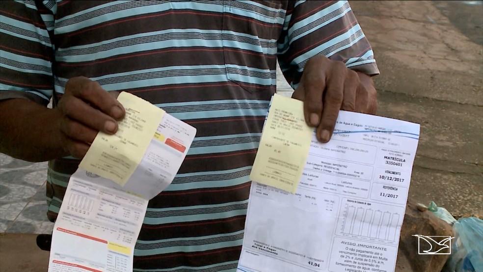 O aposentado Osmar mostra as contas de água e luz que as companias não registraram o pagamento por causa do golpe (Foto: Reprodução/TV Mirante)