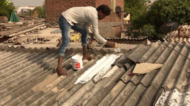 A pintura de telhados com tinta reflexiva branca é apontada como uma das soluções para reduzir o calor, mas ter banheiros internos também é visto como fundamental para deixar as mulheres menos vulneráveis (Foto: BBC)