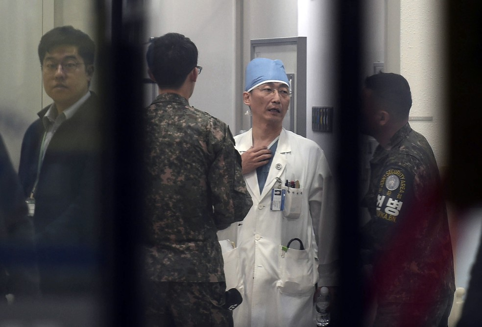 -  Soldados sul-coreanos conversam com médico que estaria atendendo desertor da Coreia do Norte  Foto: Lee Jung-son/Newsis/AP