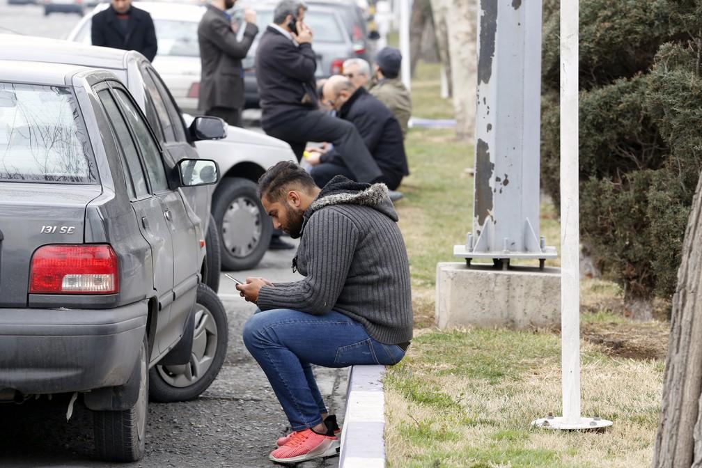 Familiares de vítimas de avião que caiu no Irã aguardam notícias em frente de mesquita próxima ao aeroporto do Teerã  (Foto: ATTA KENARE / AFP)