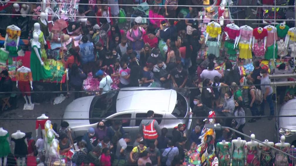 Carros passam pela multidão que se aglomera em via do Brás  — Foto: Reprodução/TV Globo
