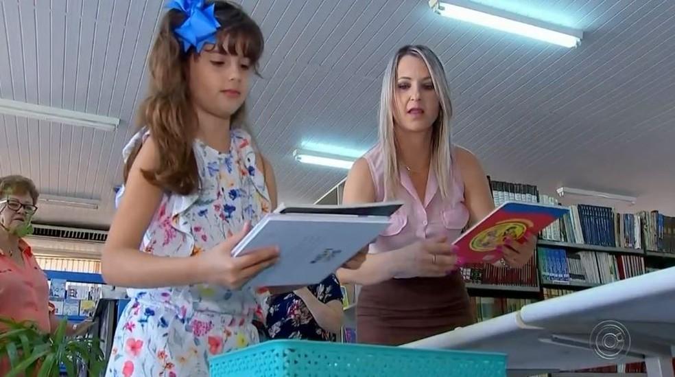 """Maria Laura Rached ao lado de Daniela Martelini, coordenadora da biblioteca, durante a doação: """"Agora podemos atrair mais crianças"""" — Foto: TV TEM/Reprodução"""