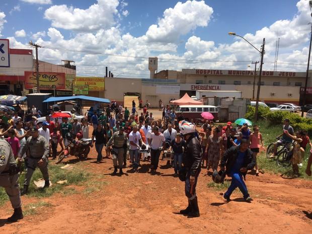 Criança baleada por policial civil é carregada por moradores, em Goiás (Foto: Bárbara Lins/TV Globo)