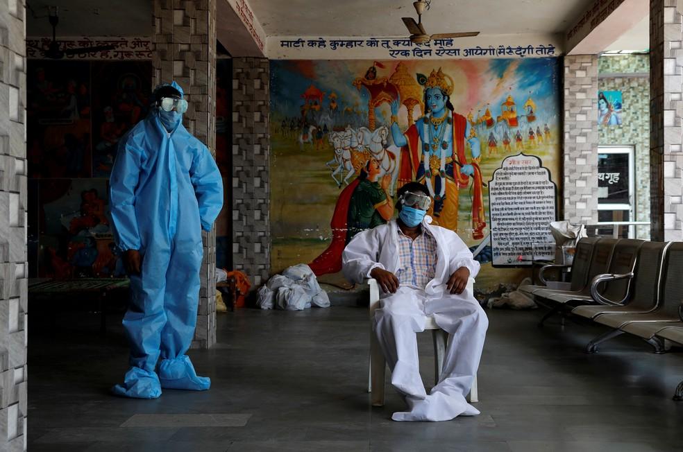 3 de julho - Um padre e um trabalhador usam equipamento de proteção individual (EPI) em um crematório, em meio à pandemia do coronavírus, em Nova Déli, na Índia — Foto: Anushree Fadnavis/Reuters