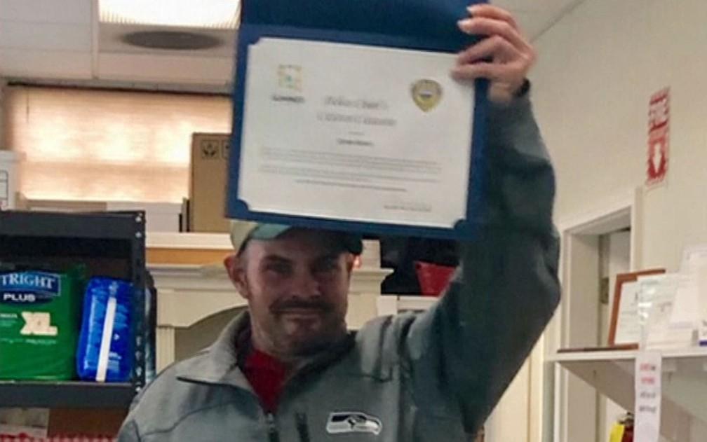 Kevin Booth exibe certificado após ser homenageado no Sumner Food Bank, em Washington — Foto: Reprodução/NBC