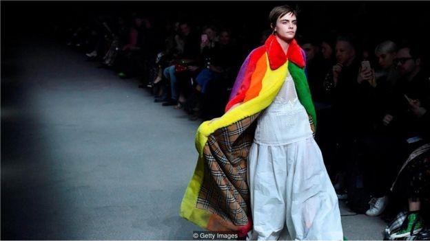 Cara Delevingne desfilou usando a capa de arco-íris da Burberry, feita com pele artificial, peça que foi destaque no desfile outono/inverno de Londres (Foto: GETTY IMAGES/via BBC News Brasil)