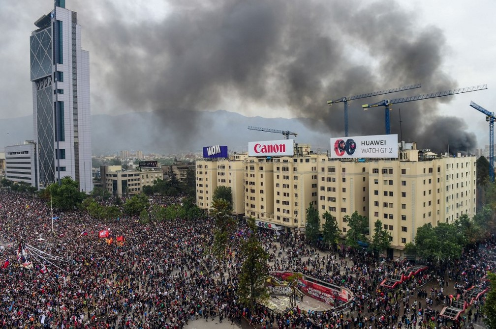 Manifestantes protestam no centro de Santiago, enquanto incêndio atinge construção clássica da capital do Chile nesta sexta-feira (8) — Foto: Martin Bernetti/AFP