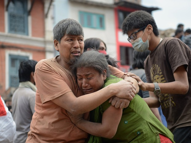 Homem e mulher se abraçam na praça Durbar, em Katmandu (Foto: Prakash Mathema / AFP)