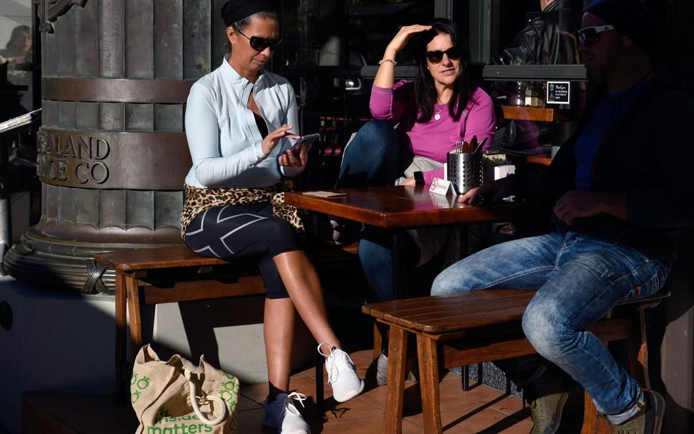 Pessoas se sentam em café ao ar livre em Nelson, na Nova Zelândia, no primeiro dia após o fim das regulamentações depois de o país ser declarado livre do coronavírus, na terça-feira (9) — Foto: Tatsiana Chypsanava / Reuters