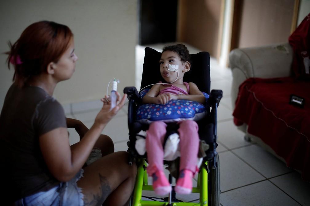 Rosana Vieira Alves, de 28 anos, alimenta a filha de dois anos Luana Vieira, que nasceu com microcefalia — Foto: Ueslei Marcelino/Reuters