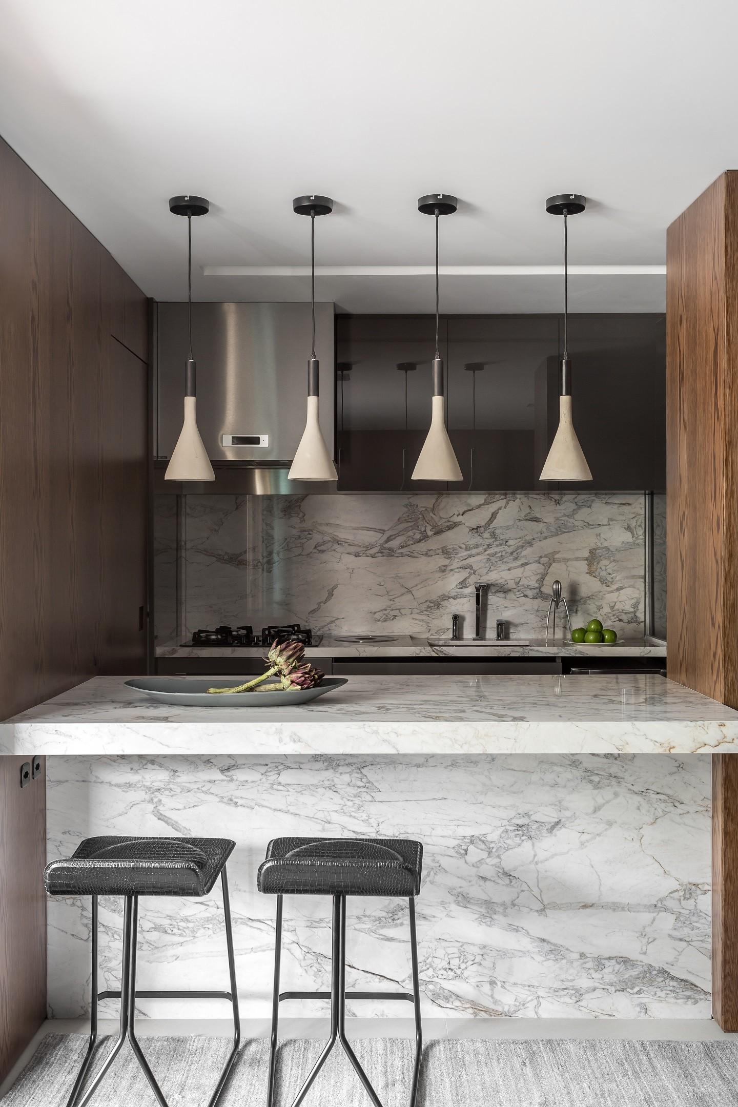 Bancada de mármores, bancos pretos, luminárias e acessórios de cozinha.