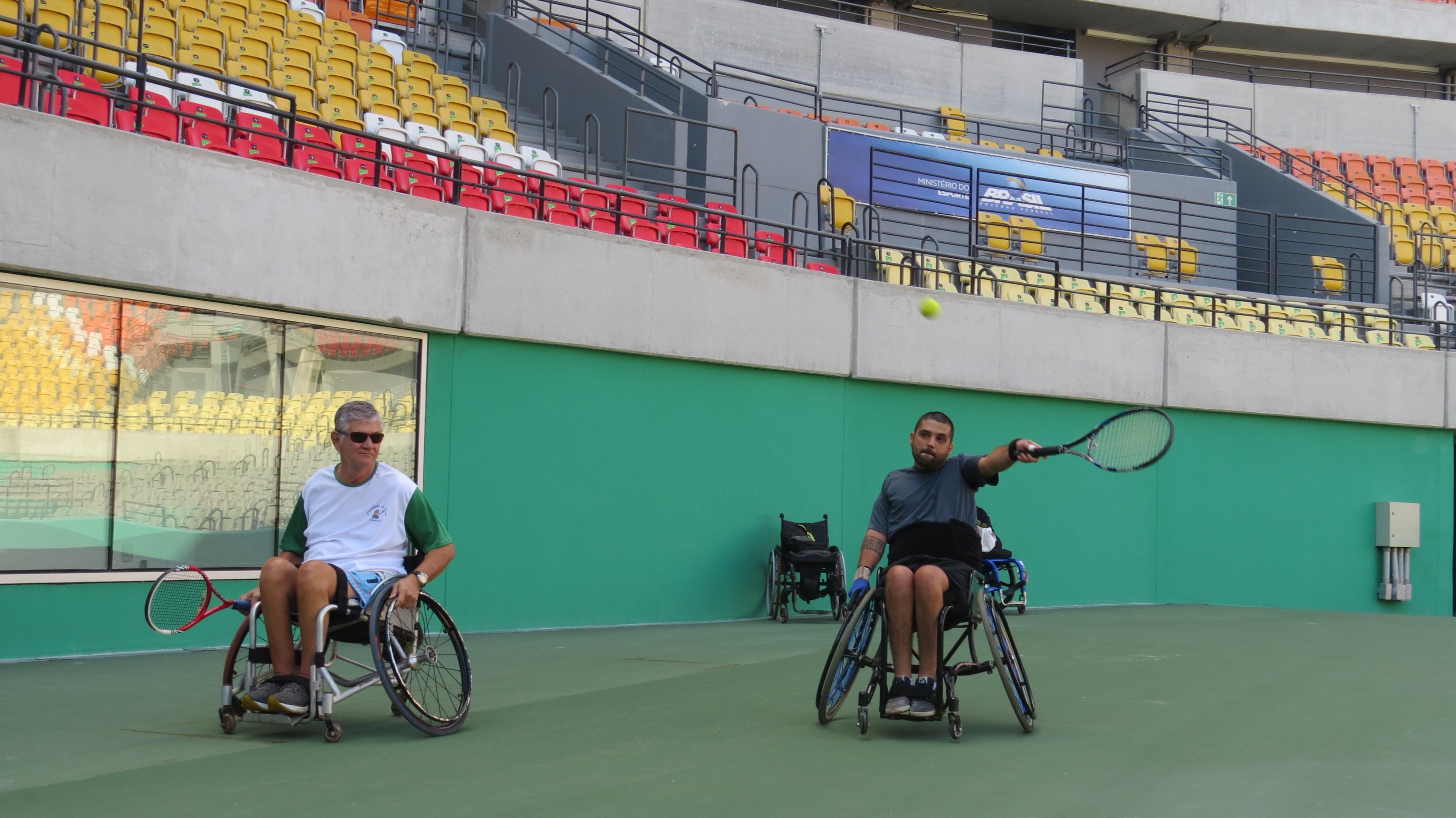 Observado por Paulo Emílio, Vinicius Pontes devolve a bola na quadra central do Parque Olímpico