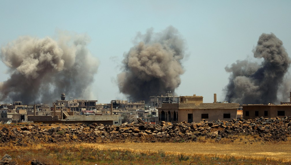 Fumaça é vista saindo de prédios na cidade de Hirak após bombardeio (Foto: Alaa al-Faqir/Reuters)