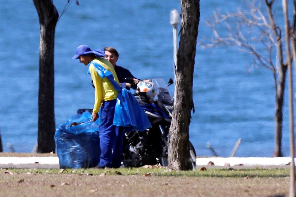 Sem máscara, o presidente Jair Bolsonaro conversa com funcionário do Palácio da Alvorada, em Brasília, após tirar o capacete durante passeio de moto dentro da área do palácio — Foto: Adriano Machado/Reuters