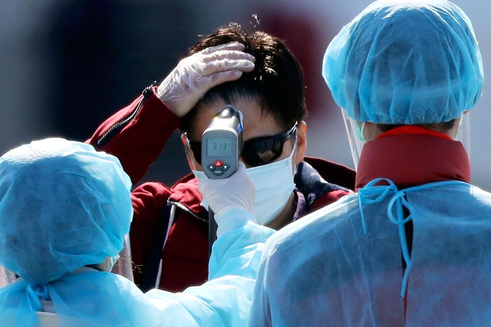 Funcionário com traje de proteção mede a temperatura de passageiros que desembarcaram do navio Diamond Princess, que fica ficou de quarentena em Yokohama, no Japão   — Foto: Eugene Hoshiko/AP