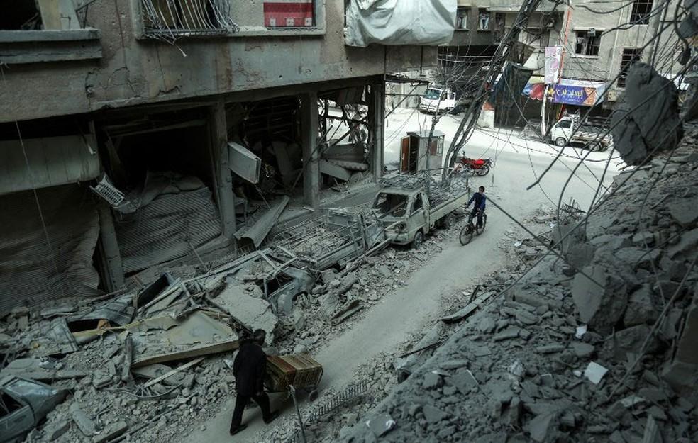 Foto mostra homem passando por destroços em Duma, na região de Guta Oriental, na quinta-feira (8)  (Foto: Hamza Al-Ajweh / AFP)