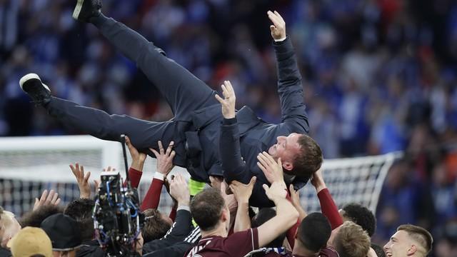 Brendan Rodgers é levantado por jogadores do Leicester no gramado