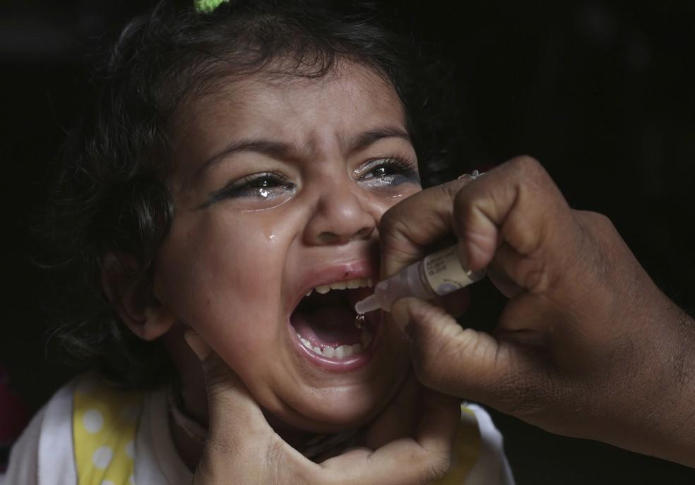 Agente de saúde vacina uma criança contra poliomielite (Foto: K.M. Chaudary/AP)