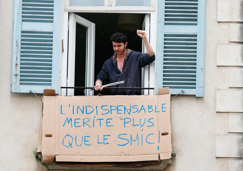 Homem coloca placa improvisada com a mensagem 'O essencial merece mais do que um salário mínimo', na cidade de Bayonne, no sudeste da França, nesta sexta-feira, 1º de Maio — Foto:  Bob Edme/AP