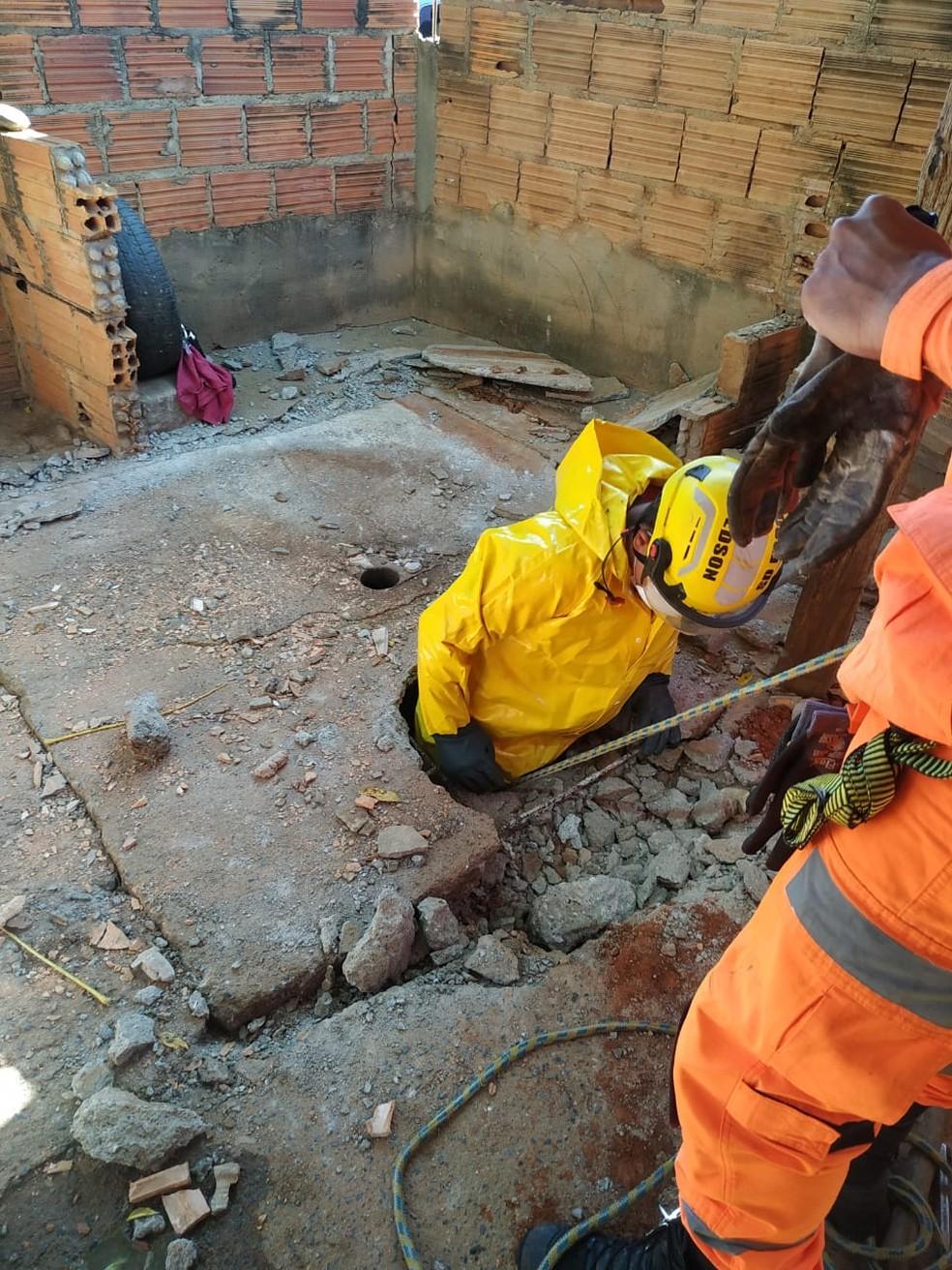 Militar desce em fossa para resgatar filhotes de cachorro — Foto: Corpo de Bombeiro/Divulgação