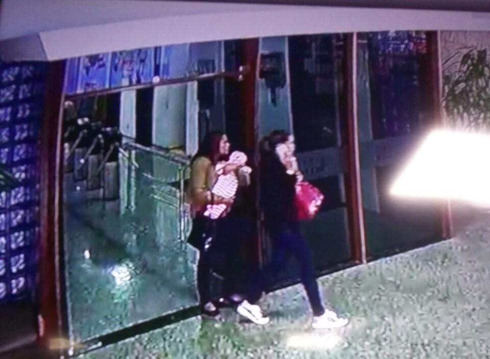 Foto da mulher com o bebê no colo saindo de prédio, em Brasília (Foto: PMDF/Divulgação)