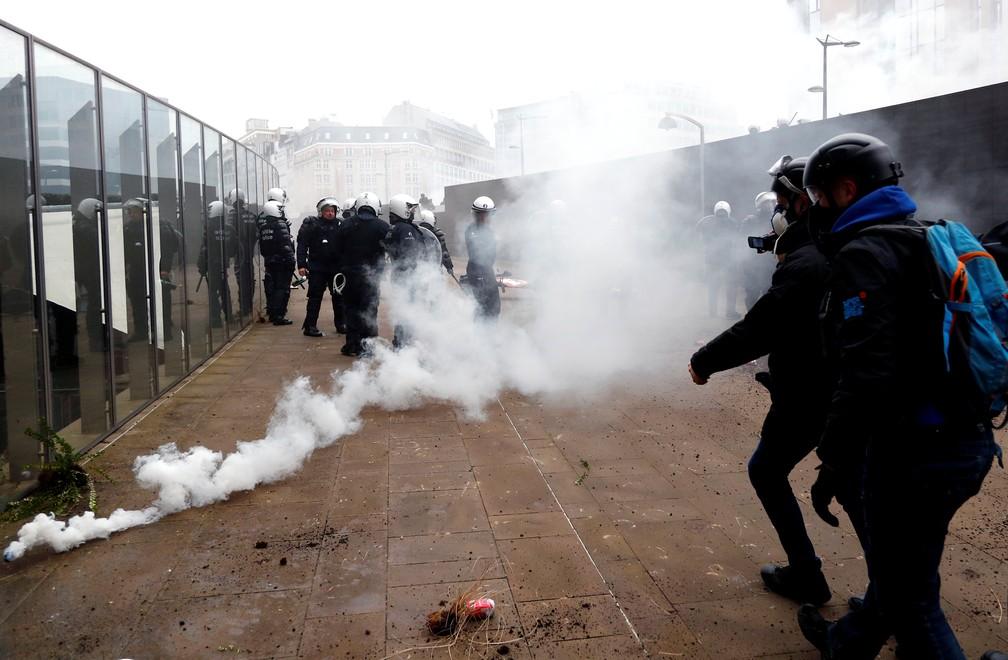 Policial joga bomba de gás lacrimogêneo contra manifestantes em protesto contra Pacto de Marrakesh em Bruxelas, na Bélgica — Foto: Francois Lenoir/Reuters