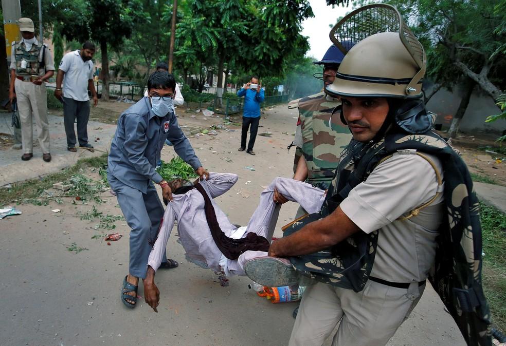 Membros das forças de segurança carregam homem ferido em combates na Índia (Foto: REUTERS/Cathal McNaughton)