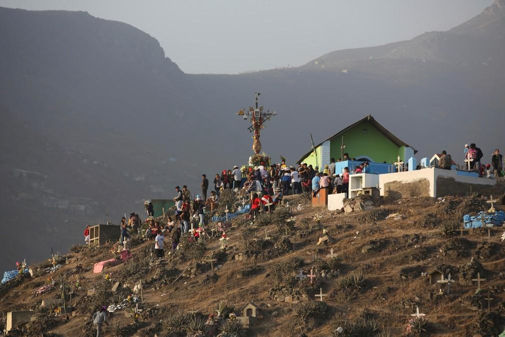 Pessoas caminham durante as celebrações do Dia dos Mortos no cemitério Nueva Esperanza em Lima, no Peru, nesta sexta (1º) — Foto: Martin Mejia/AP