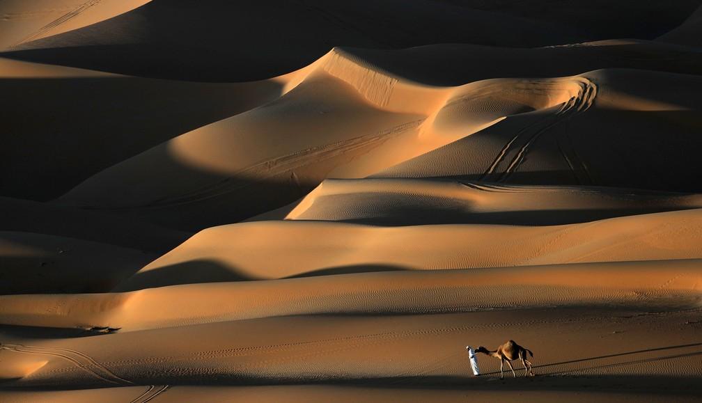2 de janeiro - Um homem caminha pelo deserto de Liwa, cerca de 250 quilômetros a oeste do Golfo de Abu Dhabi, nos Emirados Árabes Unidos, durante o Festival das Dunas de Moreeb. O evento, que atrai participantes de toda a região do Golfo, inclui uma variedade de raças e atividades destinadas a promover o folclore do país (Foto: Karim Sahib/AFP)
