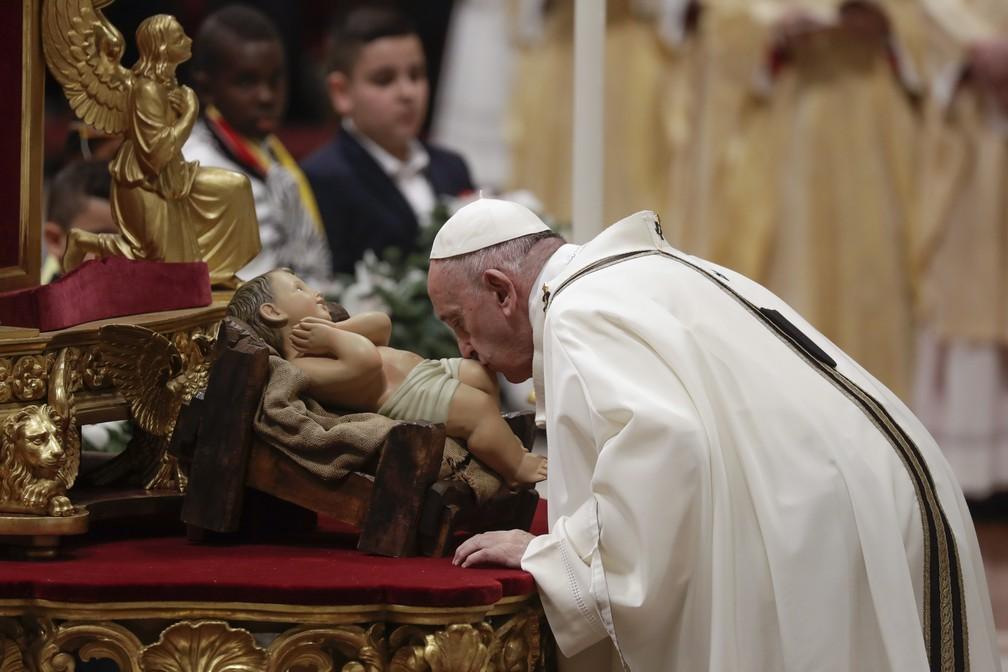 Papa Francisco beija uma estátua do menino Jesus enquanto celebra missa na véspera de Natal na Basílica de São Pedro, no Vaticano9. ( — Foto: AP Photo/Alessandra Tarantino