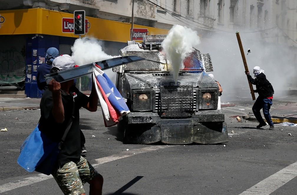 Manifestantes com rosto coberto atacam blindado de forças de segurança durante protesto em Valparaíso, no Chile, nesta quarta-feira (24) — Foto: Rodrigo Garrido/Reuteres