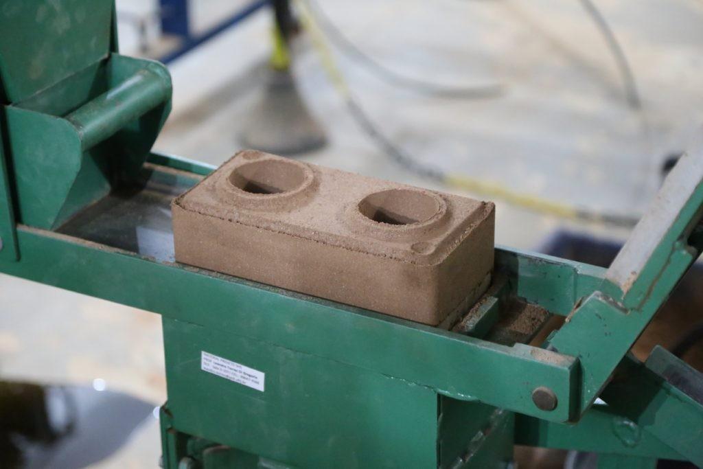 O tijolo solo-cimento pode ser produzido a partir de uma máquina de prensa manual (Foto: Divulgação)