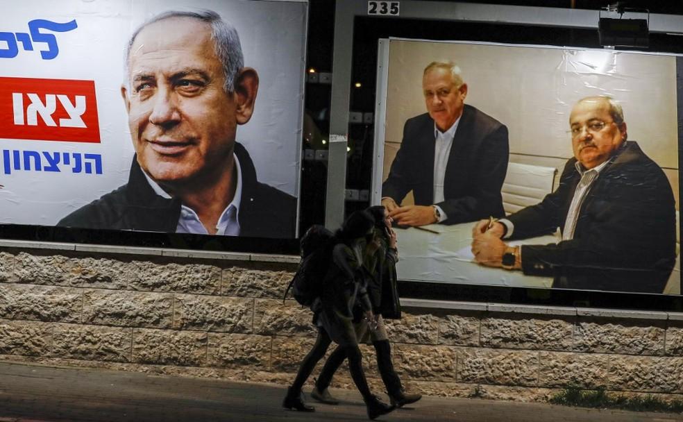 Cartaz da campanha de Benjamin Netanyahu (à esquerda) ao lado de outdoor que mostra Benny Gantz sentado ao lado de líder de partido pró-árabe, em foto de fevereiro de 2020 — Foto: Ahmad Gharabli/AFP