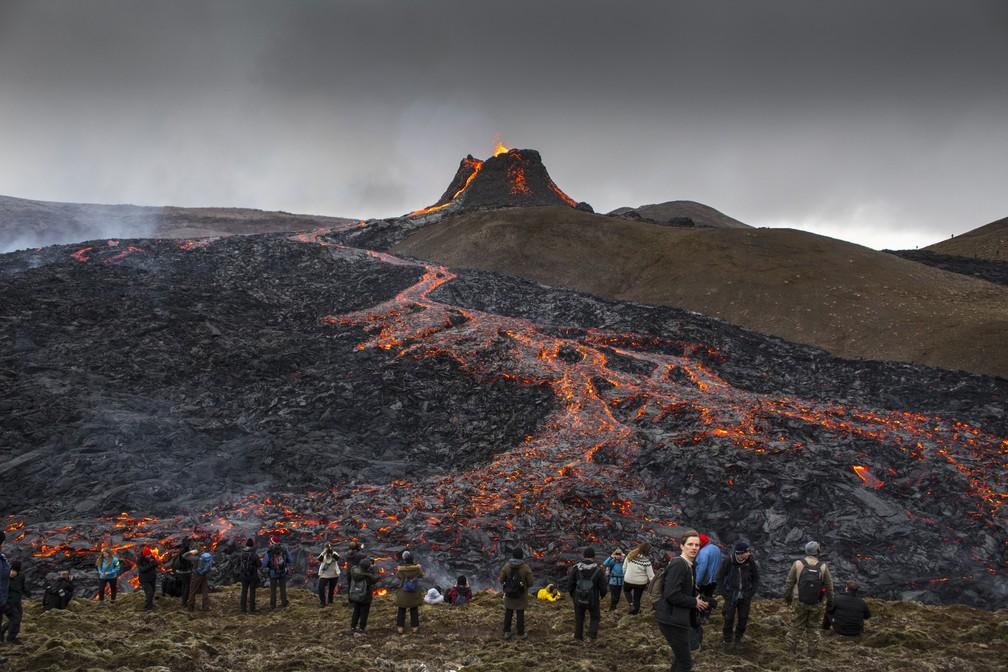 Curiosos assistem e tiram fotos de vulcão na Islândia enquanto a lava flui da erupção na península de Reykjanes na terça-feira (23) — Foto: Marco Di Marco/AP