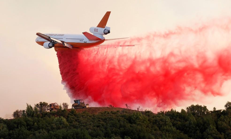 Um avião DC-10 despeja retardador de fogo ao longo do topo de uma colina para proteger dois tratores que estavam na direção do incêndio florestal no complexo de Mendocino, perto de Lakeport, na Califórnia, EUA  (Foto: Fred Greaves/Reuters)
