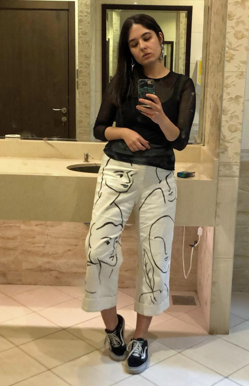 Jéssica posa para uma selfie com um par de calças que ela mesma pintou, em Dubai — Foto: Arquivo pessoal/Jéssica Duarte