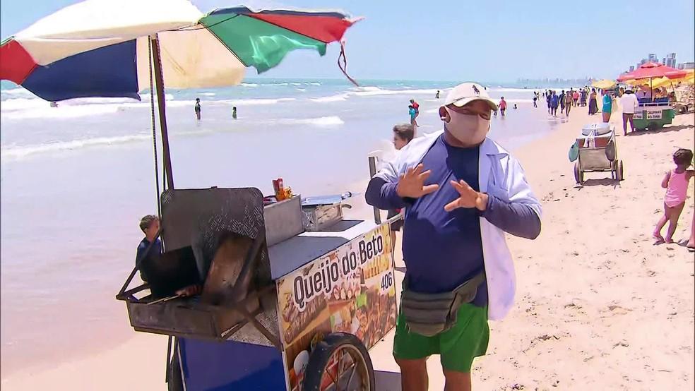 Ambulante José Roberto Ramos pede que clientes cumpram protocolo contra a Covid-19 na praia de Boa Viagem, no Recife — Foto: Reprodução/TV Globo