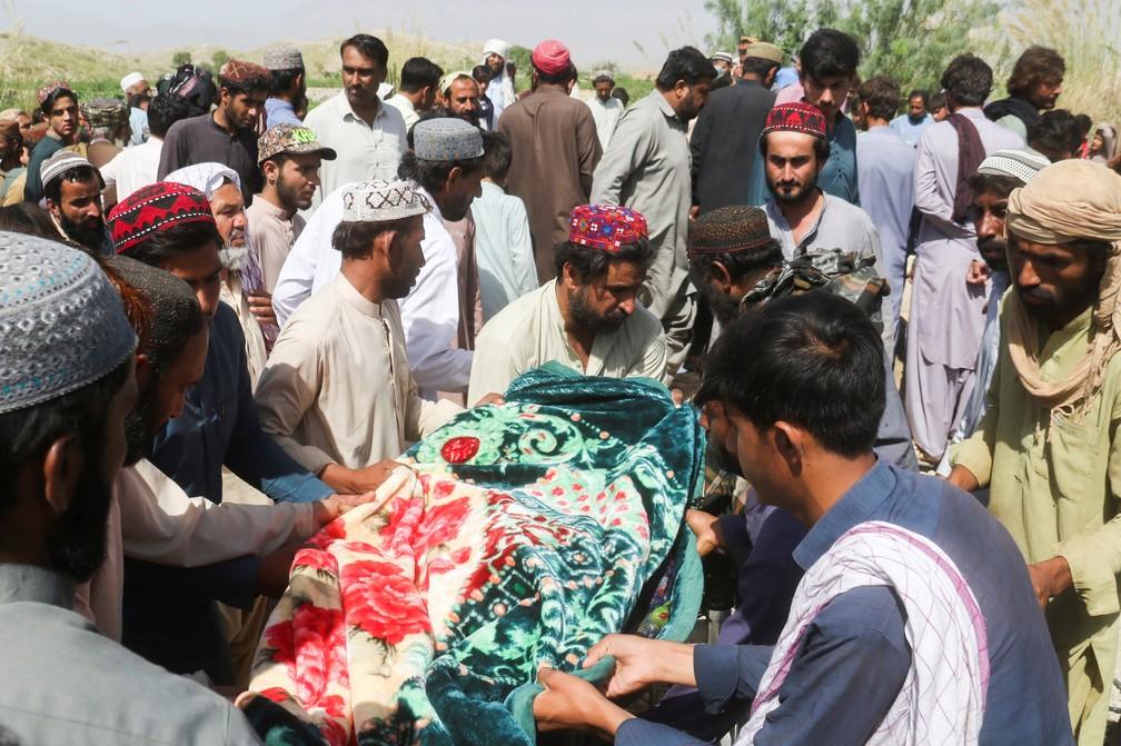 Homens carregam corpo de uma das vítimas dos terremotos no Paquistão durante funeral em Harnai em 7 de outubro de 2021 — Foto: Naseer Ahmed/Reuters