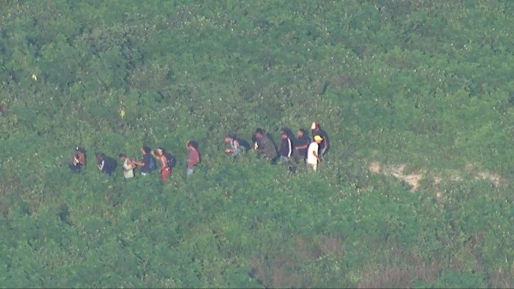Homens fogem por área de mata na Cidade de Deus — Foto: Reprodução/TV Globo