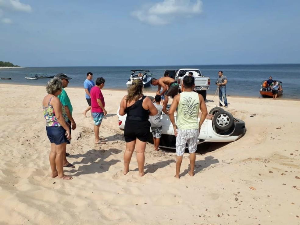 Banhistas acompanharam a tentativa de tirar o carro do desnível de areia em Alter do Chão, Pará — Foto: Reprodução/Redes Sociais