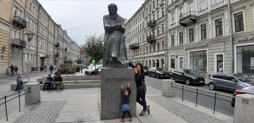 Gabriela e Olívia junto a uma estátua de Dostoiévski em São Petersburgo, na Rússia. — Foto: Arquivo pessoal/Gabriela Antunes