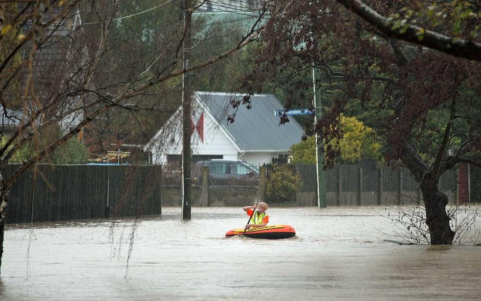 Rapaz usa uma canoa inflável em Christchurch, Nova Zelândia, após chuvas torrenciais inundarem a cidade (Foto: Mark Baker / AP Photo)