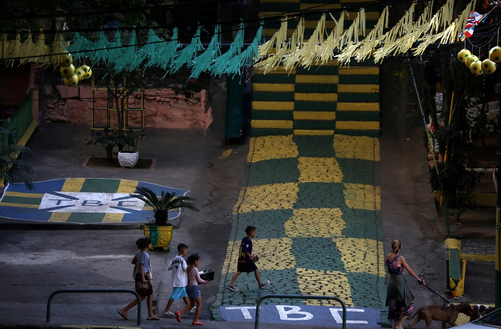 Rua recebe decoração em verde e amarelo, além de escudo da CBF pintado no chão (Foto: Pilar Olivares/Reuters)