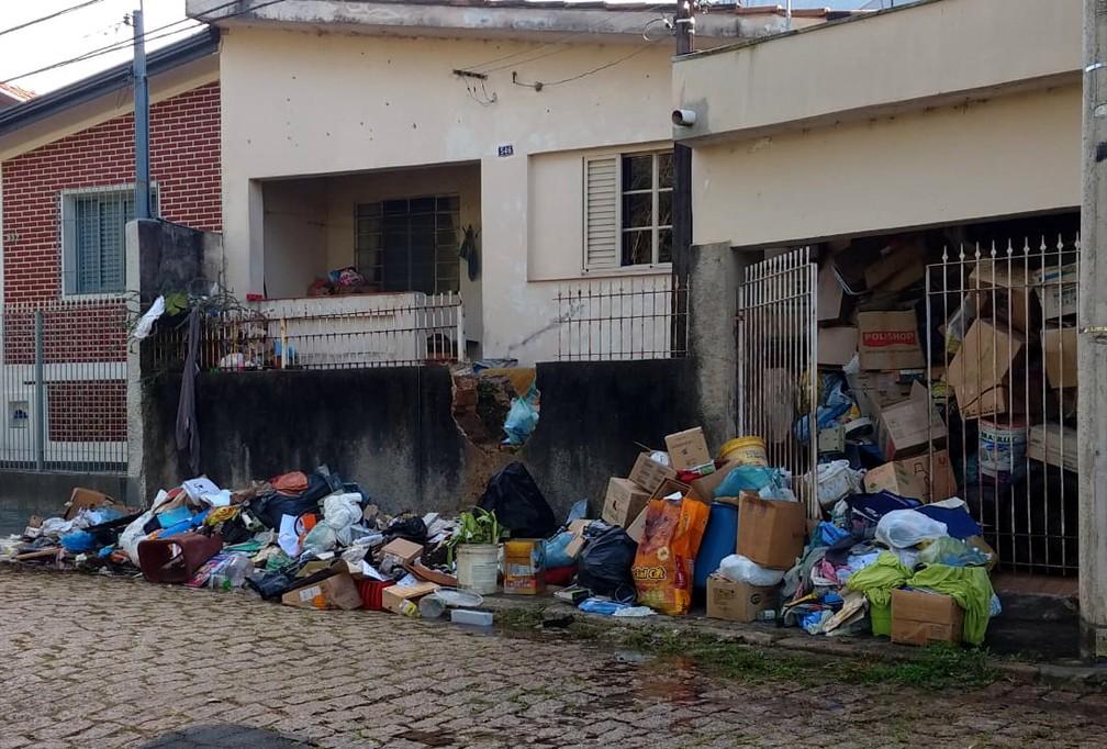 Quantidade de material é tão grande que idoso precisou abrir um buraco no muro para entrar e sair de casa — Foto: Jussara Lima/Jornal Taperá